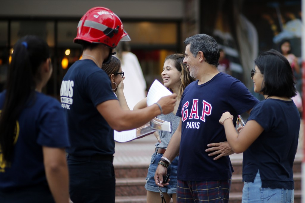 In this Jan. 13, 2019 photo, firefighter Daniel Rodriguez sells calendars to a family, in Asuncion, Paraguay. The idea for the calendar arose during a