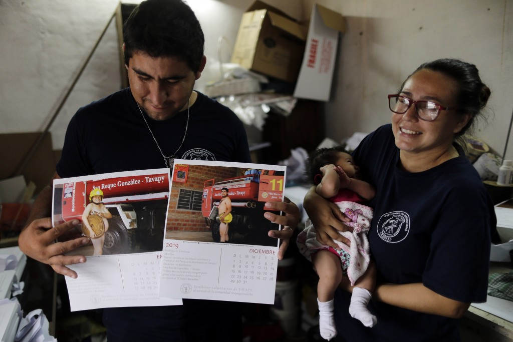 In this Jan. 12, 2019 photo, firefighter Fatima Olmedo, right, holds her two-month-old baby Samara as her husband Rodrigo Gimenez holds calendar pages