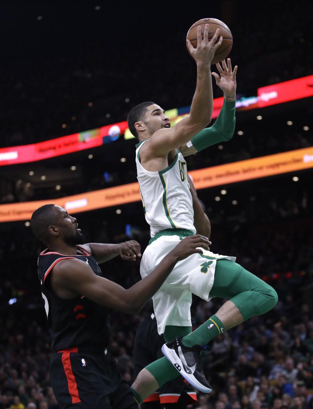 Boston Celtics forward Jayson Tatum, right, drives to the basket past Toronto Raptors forward Serge Ibaka, left, during the first quarter of an NBA ba