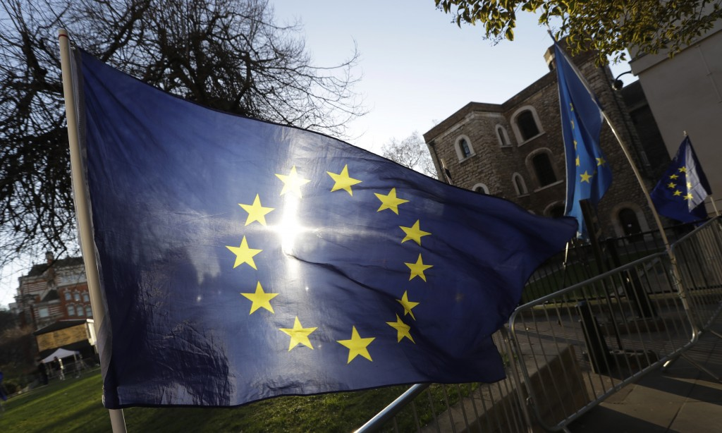 The sun shines through a European Union flag tied onto a railing near parliament in London, Thursday, Jan. 17, 2019. British Prime Minister Theresa Ma