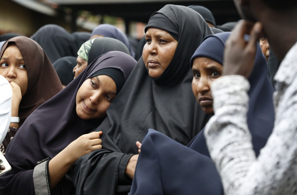 Family members including the mother of Abdalla, center, prepare to pray over the bodies of Abdalla Dahir and Feisal Ahmed, who were both killed in Tue...