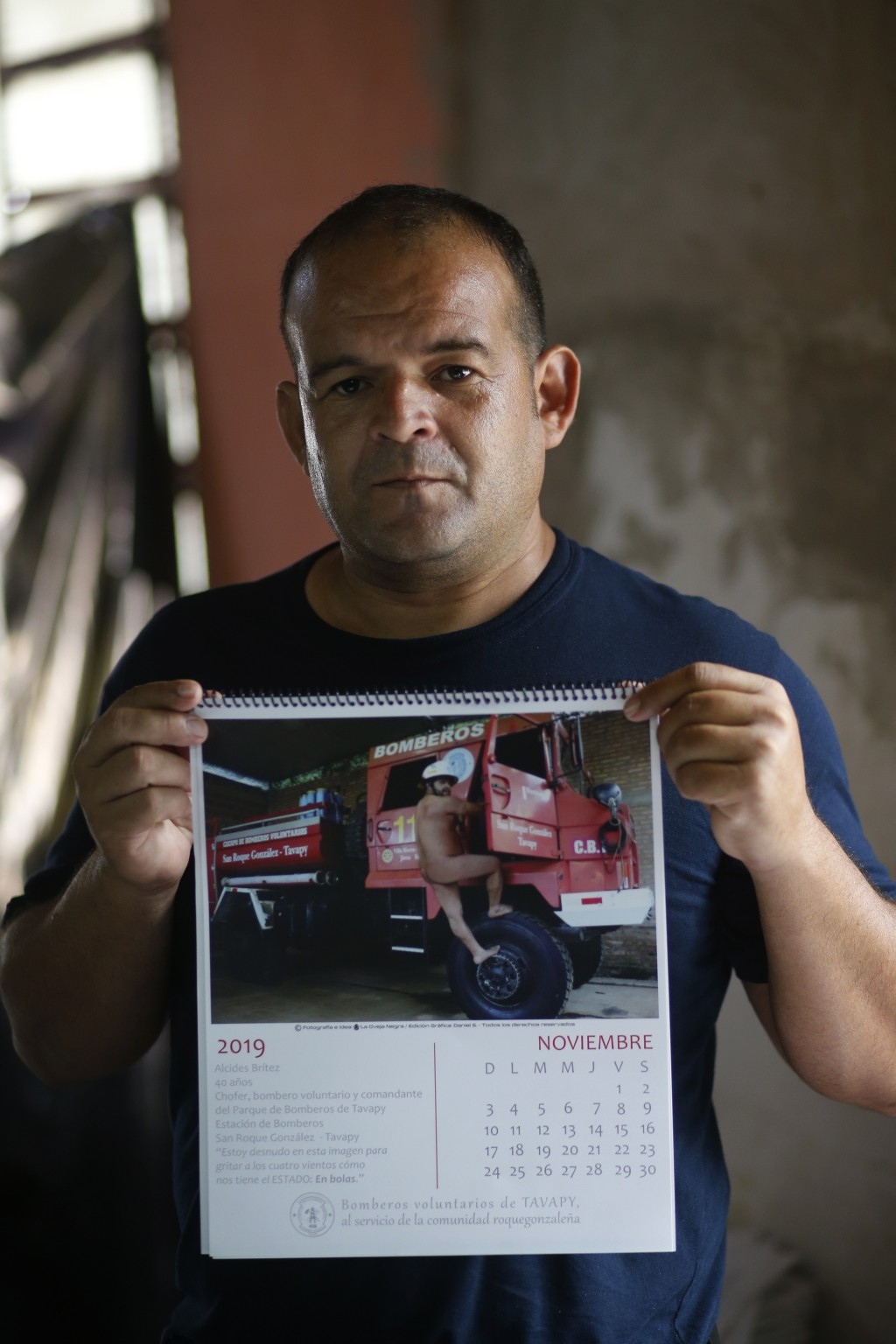 "In this Jan. 12, 2019 photo, firefighter Commander Alcides Britez holds a calendar page with a photo of himself posing nude, in Asuncion, Paraguay. ""T"