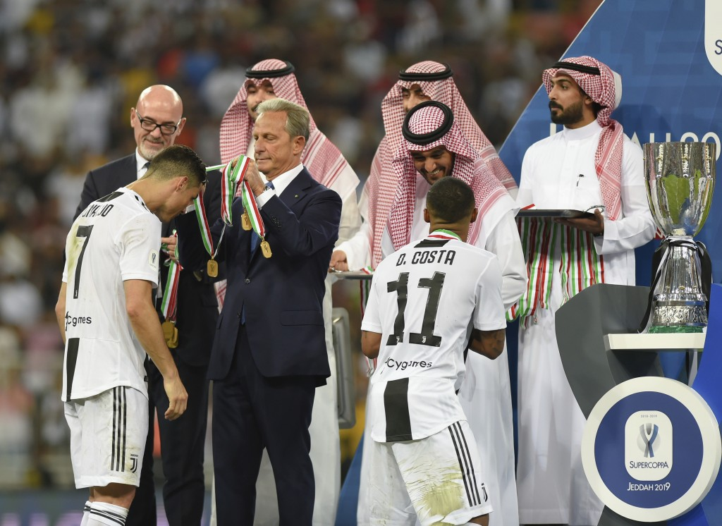 Juventus' Cristiano Ronaldo, left, and Juventus' Douglas Costa receive the winner medals end of the Italian Super Cup final soccer match between AC Mi...