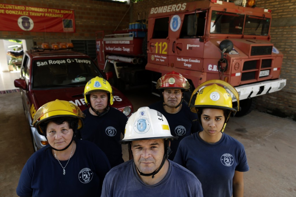 In this Jan. 13, 2019 photo, Commander Alcides Britez, center, and a group of firefighters pose for a photo at their fire station in San Roque Gonzale