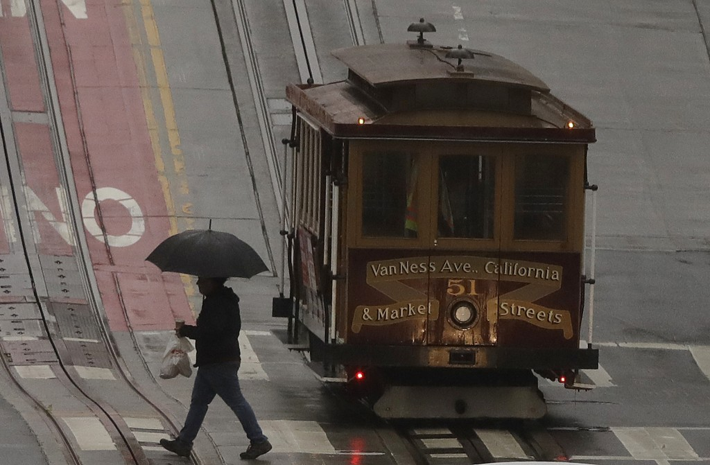 A pedestrian walks in the rain in front of a cable car in San Francisco, Wednesday, Jan. 16, 2019. A series of storms dropped rain up and down the sta