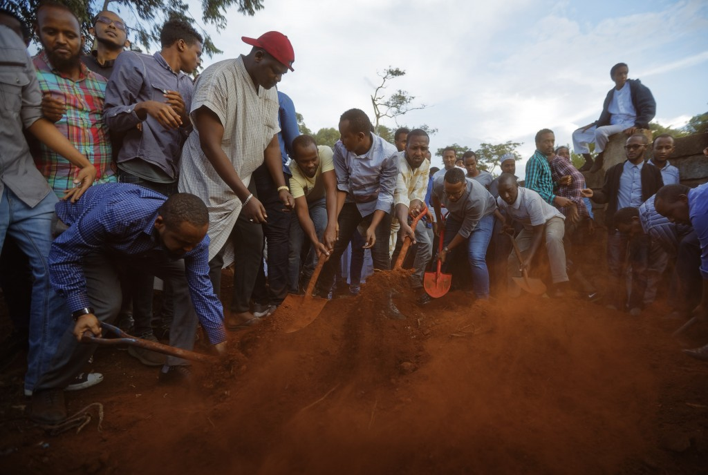 Mourners bury the body of Abdalla Dahir near to the grave of his colleague Feisal Ahmed, who were both killed in Tuesday's attack, at their funerals i...