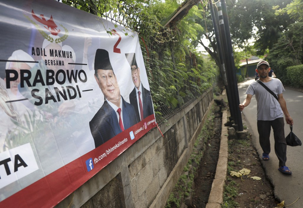 A man walks past a campaign banner for Indonesian presidential candidate Prabowo Subianto, left, and his running mate Sandiaga Uno in Jakarta, Indones