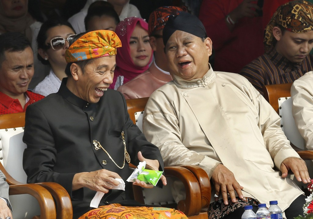 FILE - In this Sept. 23, 2018 file photo, Indonesian President Joko Widodo, left, and his contender Prabowo Subianto share a light moment during a cer