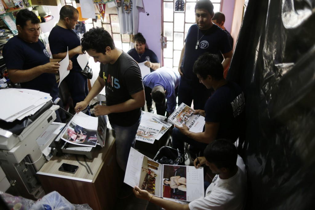 In this Jan. 12, 2019 photo, firefighters work putting calendars together in Asuncion, Paraguay. The San Roque Gonzalez fire station gets about $600 a