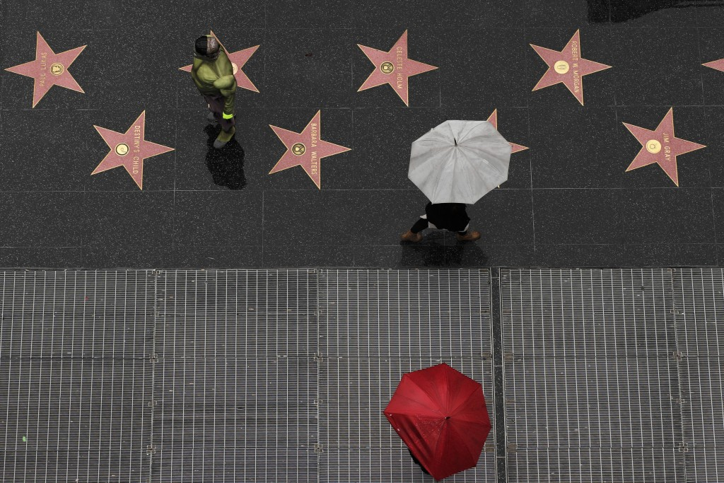 A superhero impersonator stands on the Hollywood Walk of Fame as it rains Wednesday, Jan. 16, 2019, in the Hollywood section of Los Angeles. Numerous