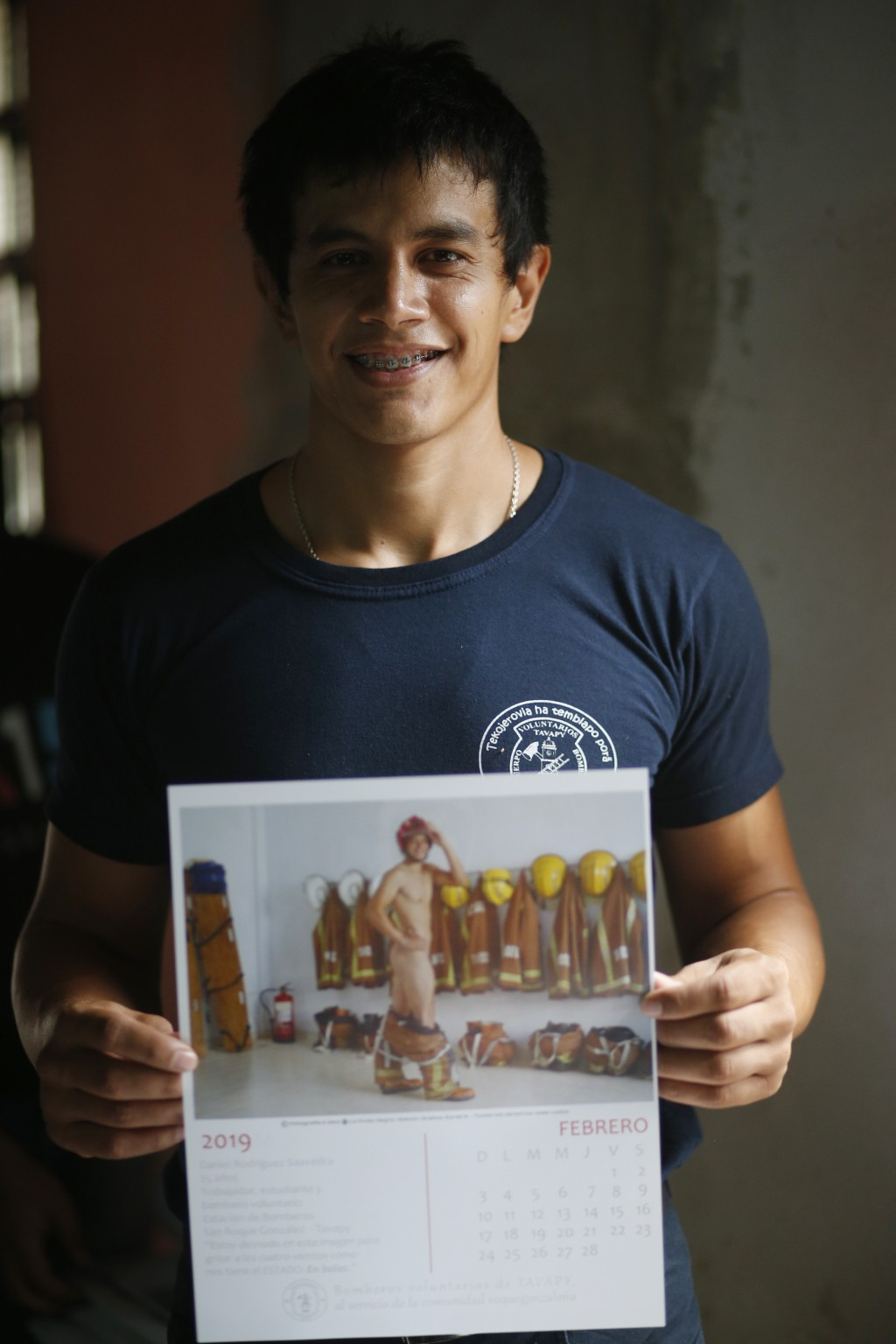 In this Jan. 12, 2019 photo, firefighter Daniel Rodriguez poses holding a calendar page with a nude photo of himself, in Asuncion, Paraguay. The capti