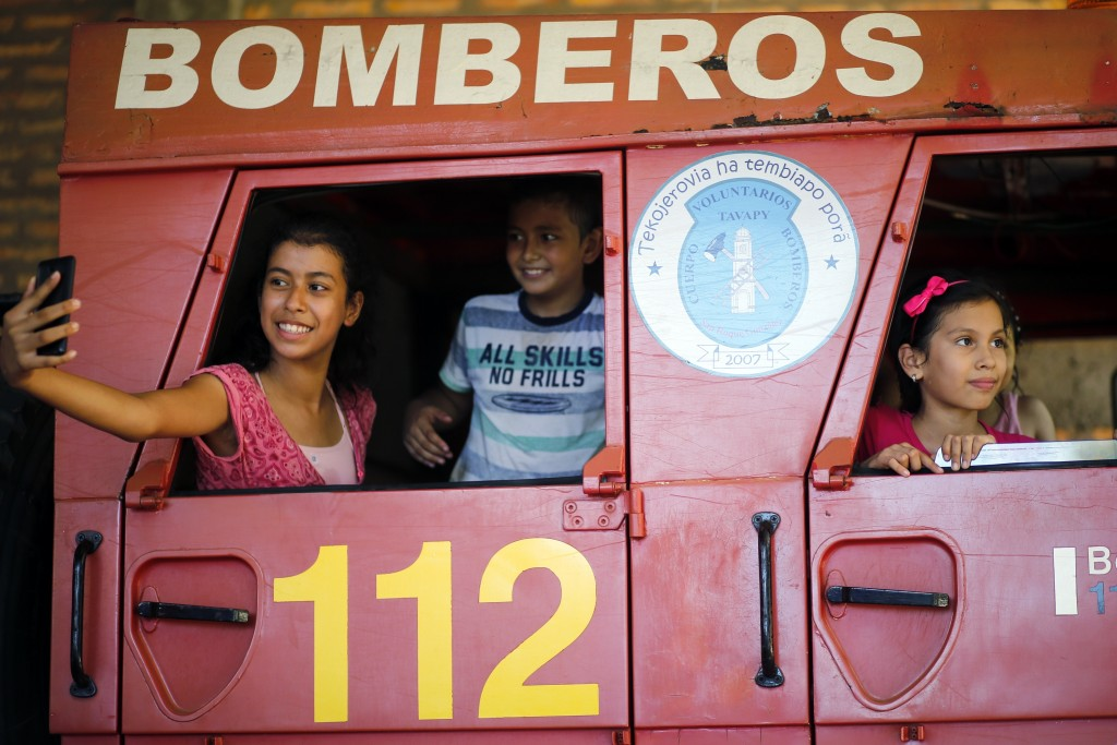 In this Jan. 13, 2019 photo, sons and daughters of firefighters take selfies inside the fire truck during a visit to the station in San Roque Gonzalez