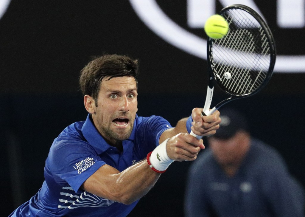 Serbia's Novak Djokovic makes a backhand return to France's Jo-Wilfried Tsonga during their second round match at the Australian Open tennis champions