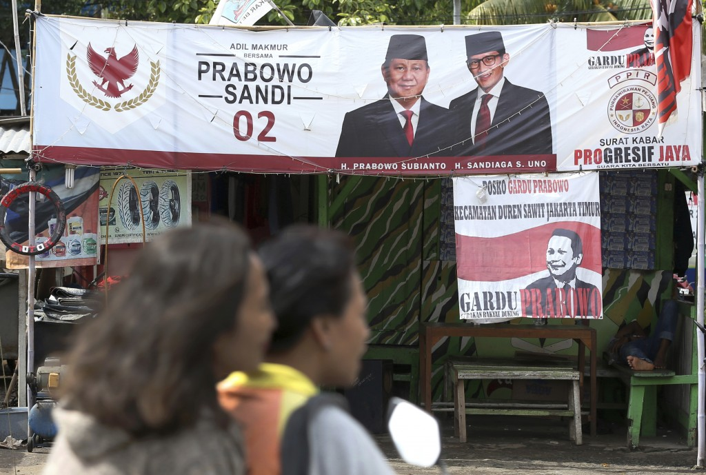 A couple rides a motorcycle past a campaign banners for Indonesian presidential candidate Prabowo Subianto, left, and his running mate Sandiaga Uno in