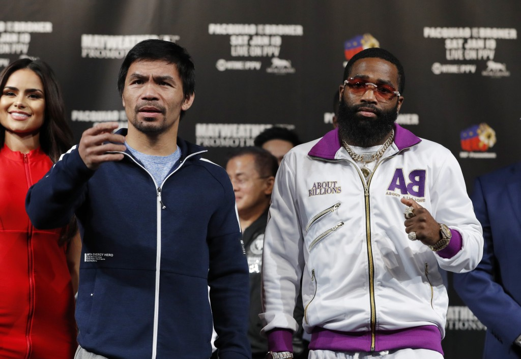 Manny Pacquiao, left, and Adrien Broner pose for photographers during a news conference Wednesday, Jan. 16, 2019, in Las Vegas. The two are scheduled