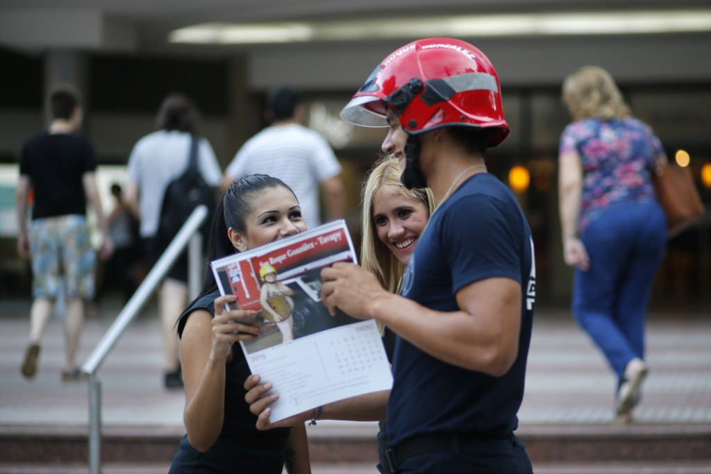 In this Jan. 13, 2019 photo, firefighter Daniel Rodriguez sells calendars to a couple of women in Asuncion, Paraguay. Firefighters in the town of San
