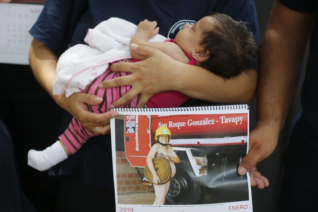 In this Jan. 12, 2019 photo, firefighter Fatima Olmedo holds her two-month-old baby Samara as her husband holds a calendar page with a photo Olmedo po