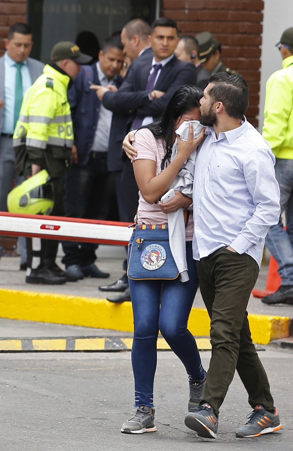 Family members of victims of a bombing embrace outside the entrance to the General Santander police academy where the bombing took place in Bogota, Co...