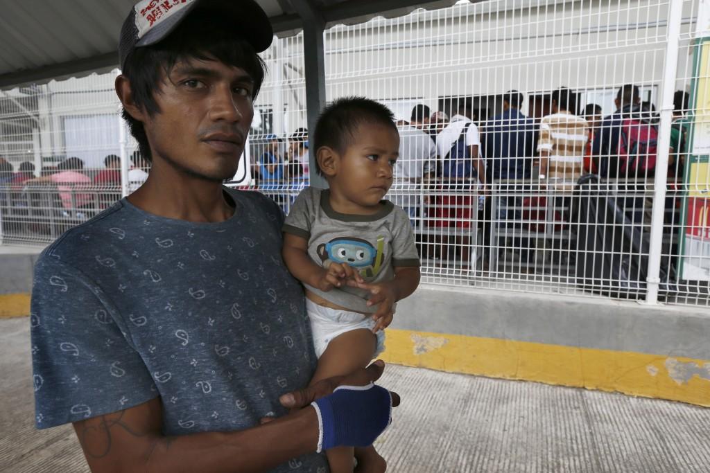 A man his son walk across the Suchiate river bridge as Central American migrants cross the border between Guatemala and Mexico, near Ciudad Hidalgo, C