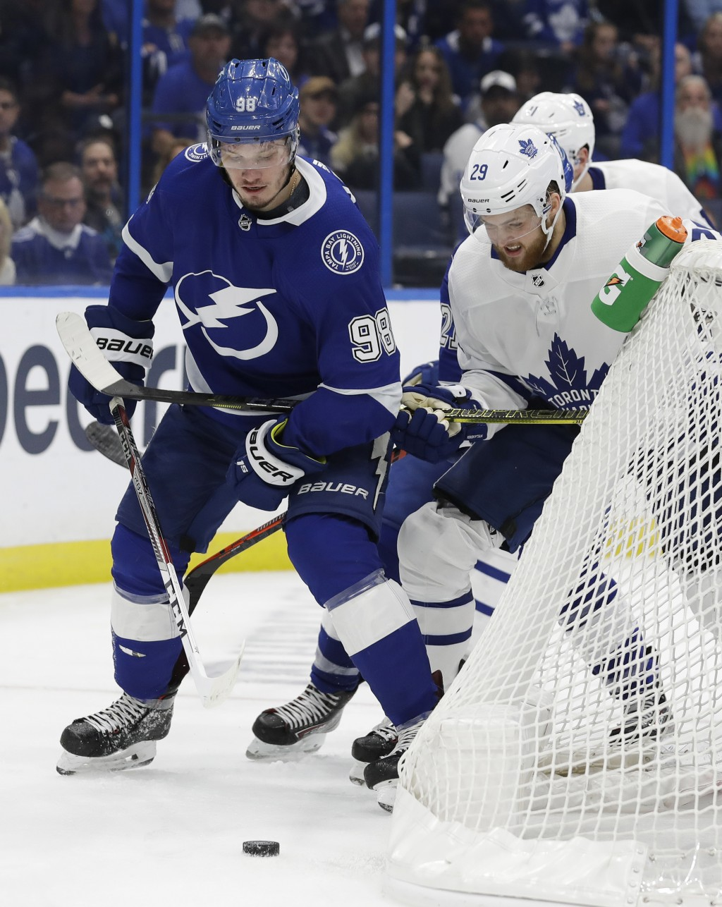 Tampa Bay Lightning defenseman Mikhail Sergachev (98) battles with Toronto Maple Leafs right wing William Nylander (29) for a loose puck behind the ne