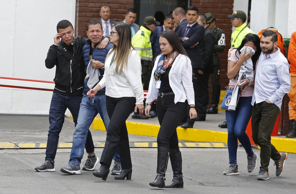 Family members of victims of a bombing cry outside the entrance to the General Santander police academy where the bombing took place in Bogota, Colomb