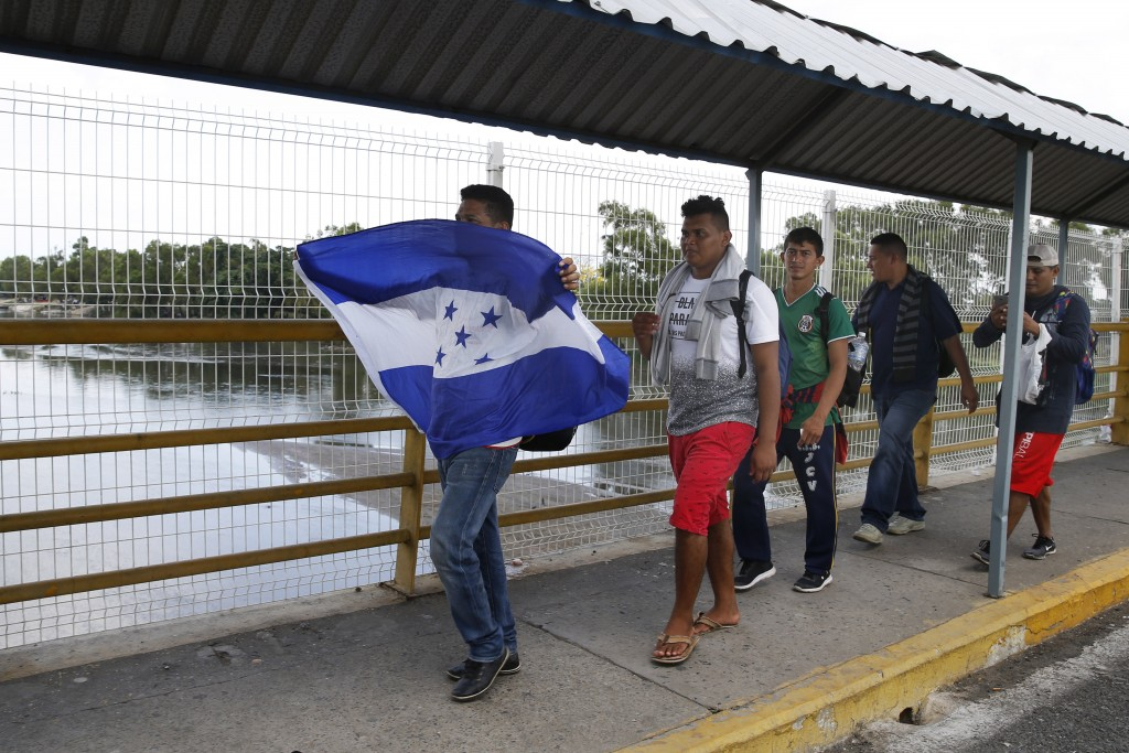 Men walk across the Suchiate river bridge with a Honduran flag as they cross the border into Mexico from Guatemala, near Ciudad Hidalgo, Chiapas State