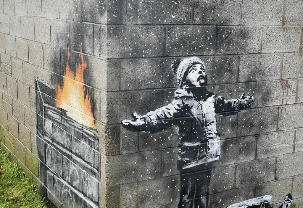FILE -  In this file photo dated Dec, 20, 2018, showing an artwork by Banksy on the side of a garage depicts a child dressed for snow playing in the f