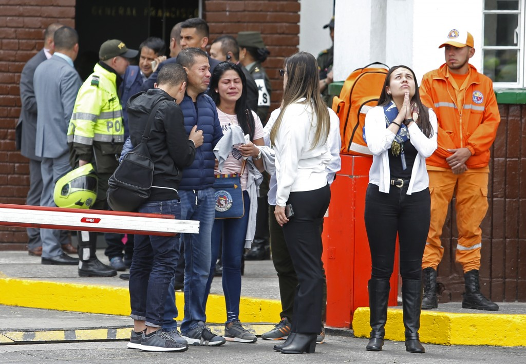 Family members of victims of a bombing gather outside the entrance to the General Santander police academy where the bombing took place in Bogota, Col