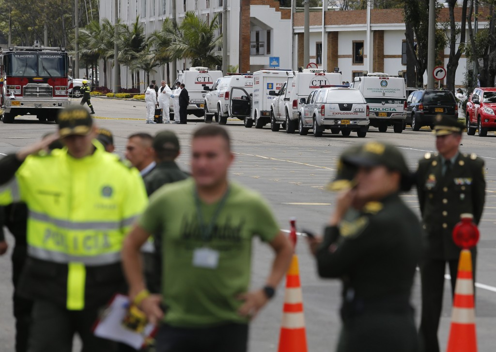 Forensic workers, behind top, work the scene of a deadly car bombing at the General Santander police academy in Bogota, Colombia, Thursday, Jan. 17, 2...