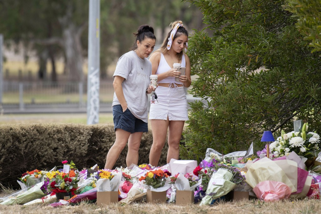 Two women stand at a floral tribute, Friday, Jan. 18, 2019, at the scene where the body of Israeli student Aiia Maasarwe was found earlier in the week