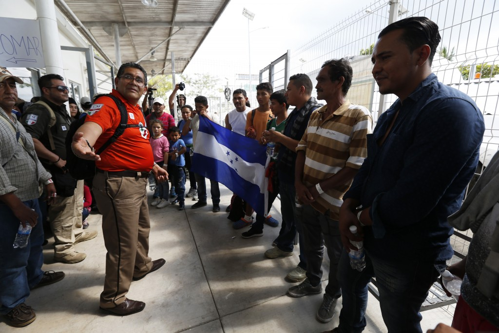 A Mexican immigration official welcomes a group of migrants as they cross the border into Mexico from Guatemala, near Ciudad Hidalgo, Chiapas State, M