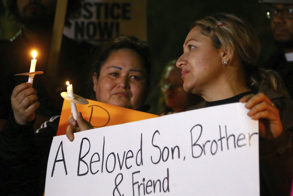 Sandra Gonzalez, left, mother of slain 14-year-old boy shot by Tempe Police, joins another family member, right, and others in front of the Tempe Poli...