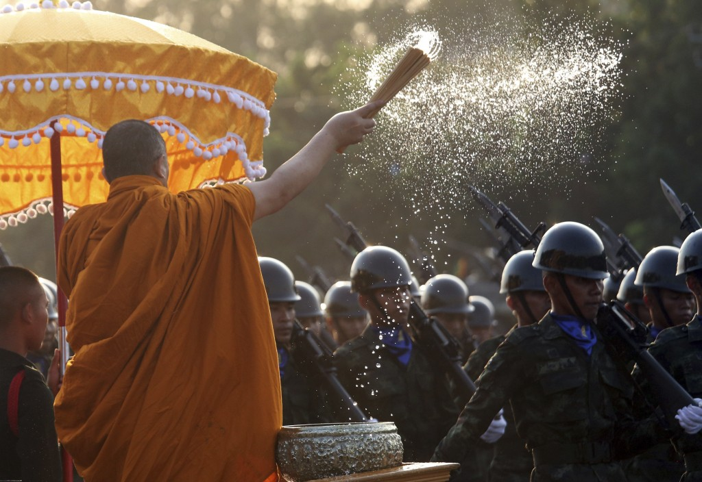 A Buddhist monk splashes holy water to Thai soldiers during the Royal Thai Armed Forces Day ceremony at a military base in Bangkok, Thailand, Friday,