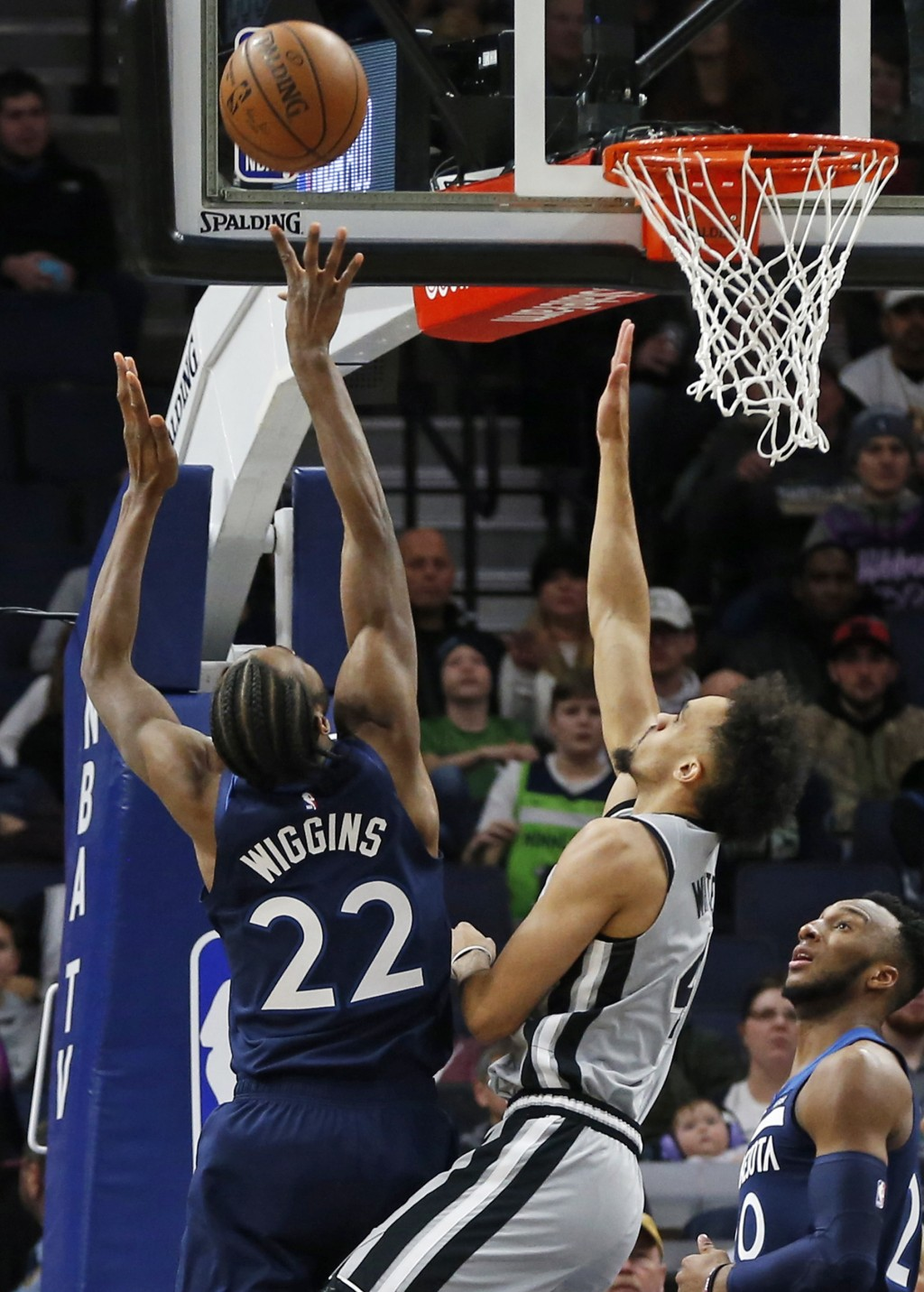 Minnesota Timberwolves' Andrew Wiggins, left, shoots as San Antonio Spurs' Derrick White defends in the first half of an NBA basketball game Friday, J...