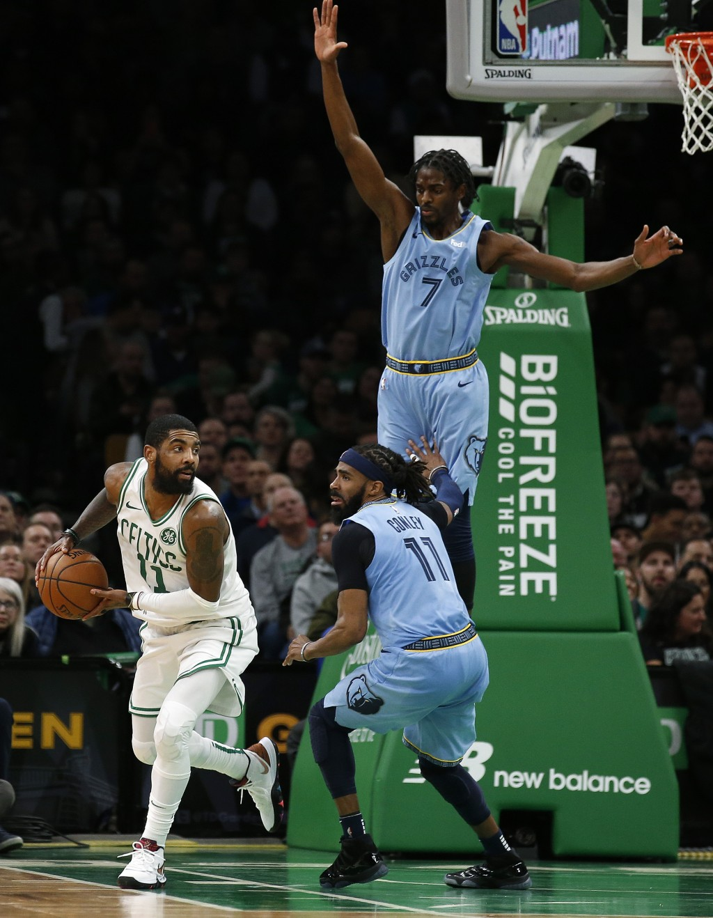 Memphis Grizzlies' Justin Holiday (7) and Mike Conley cut off Boston Celtics' Kyrie Irving's route to the basket during the second half of Boston's 12