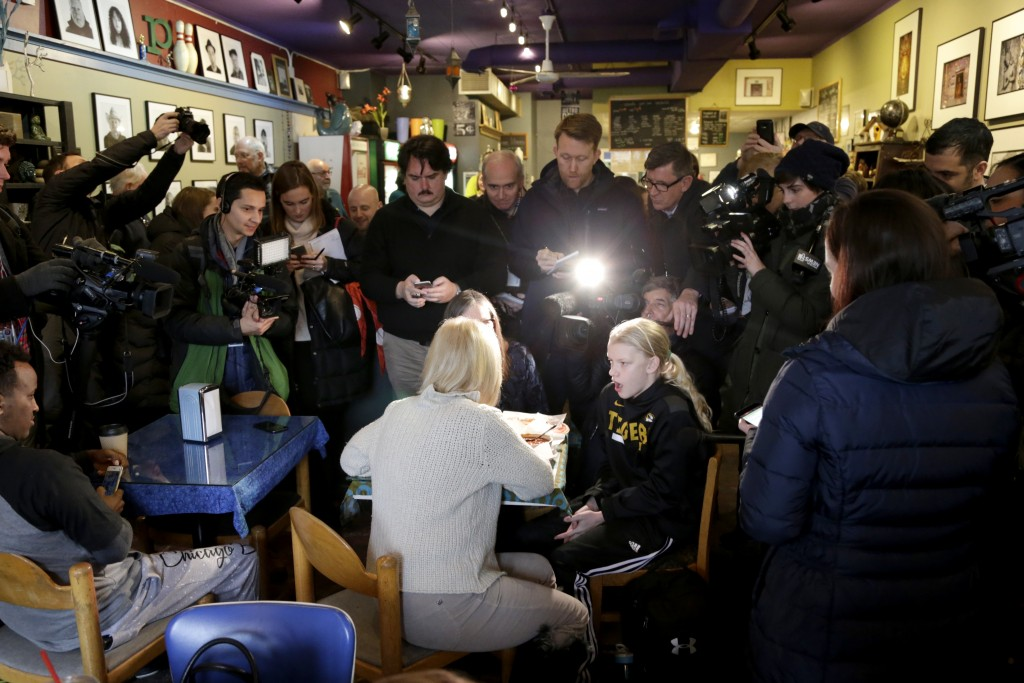 U.S. Kirsten Gillibrand, D-N.Y., with back to camera, sits down for a chat with Jeanette Hopkins, rear, and Chloe McClure, right, at the Pierce Street