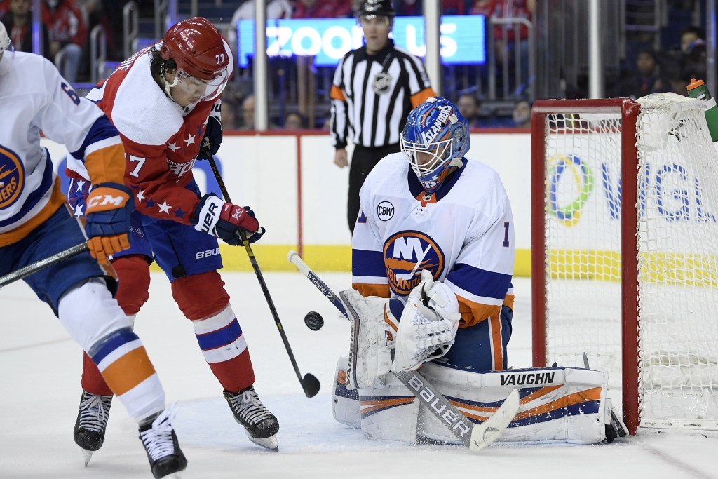 New York Islanders goaltender Thomas Greiss (1) stops the puck next to Washington Capitals right wing T.J. Oshie (77) during the second period of an N...