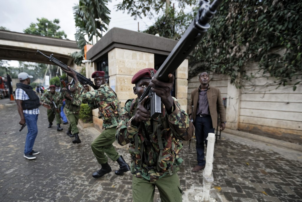 Kenyan security forces aim their weapons up at buildings as they run through a hotel complex in Nairobi, Kenya Tuesday, Jan. 15, 2019. Terrorists atta...