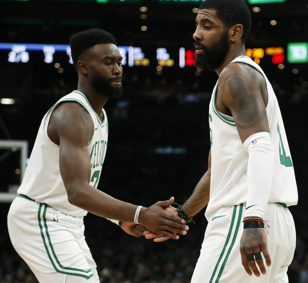 Boston Celtics' Jaylen Brown, left, congratulates Kyrie Irving after Irving hit a basket against the Memphis Grizzlies during the first quarter of an