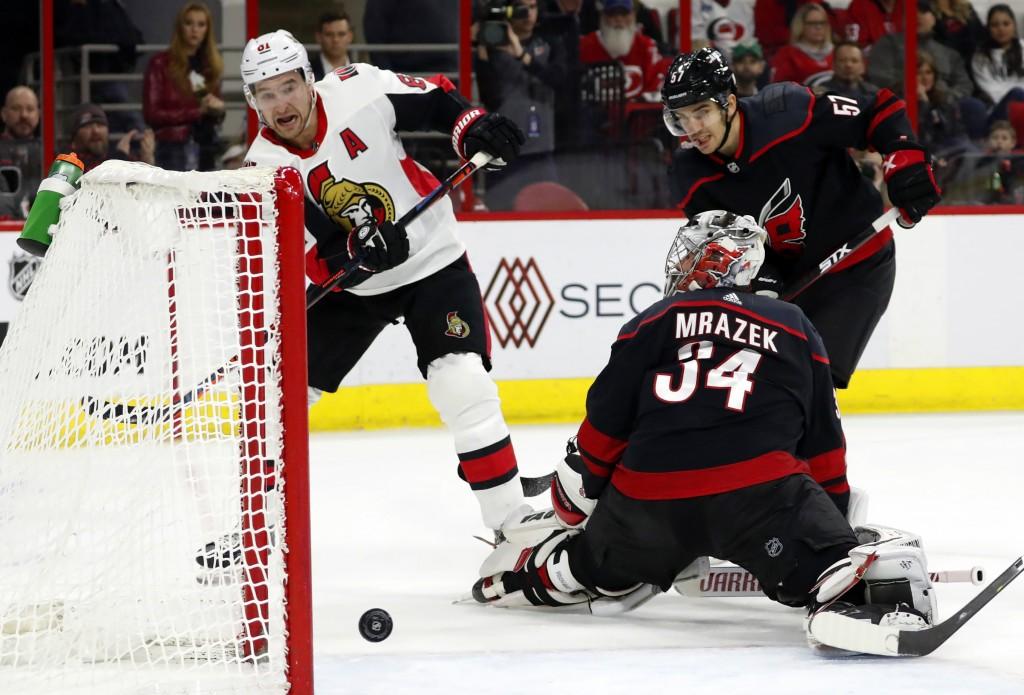 Ottawa Senators' Mark Stone (61), followed by Carolina Hurricanes' Trevor van Riemsdyk (57), shoots the puck past goaltender Petr Mrazek (34) but fail...