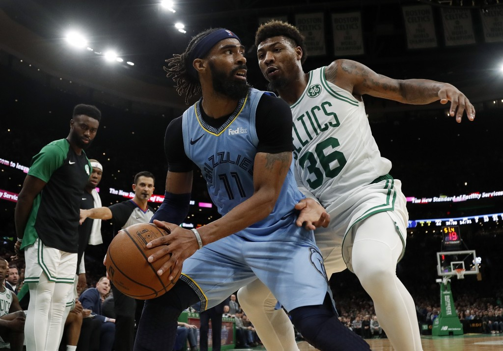 Memphis Grizzlies' Mike Conley (11) looks for a way around Boston Celtics' Marcus Smart during the second half of Boston's 122-116 win in an NBA baske
