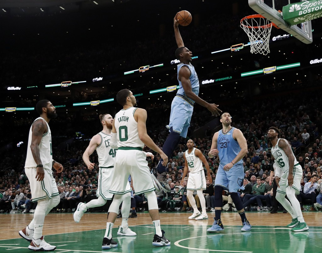 Memphis Grizzlies' Jaren Jackson Jr. goes past Boston Celtics' Jayson Tatum (0) and others for a dunk during the second half of Boston's 122-116 win i