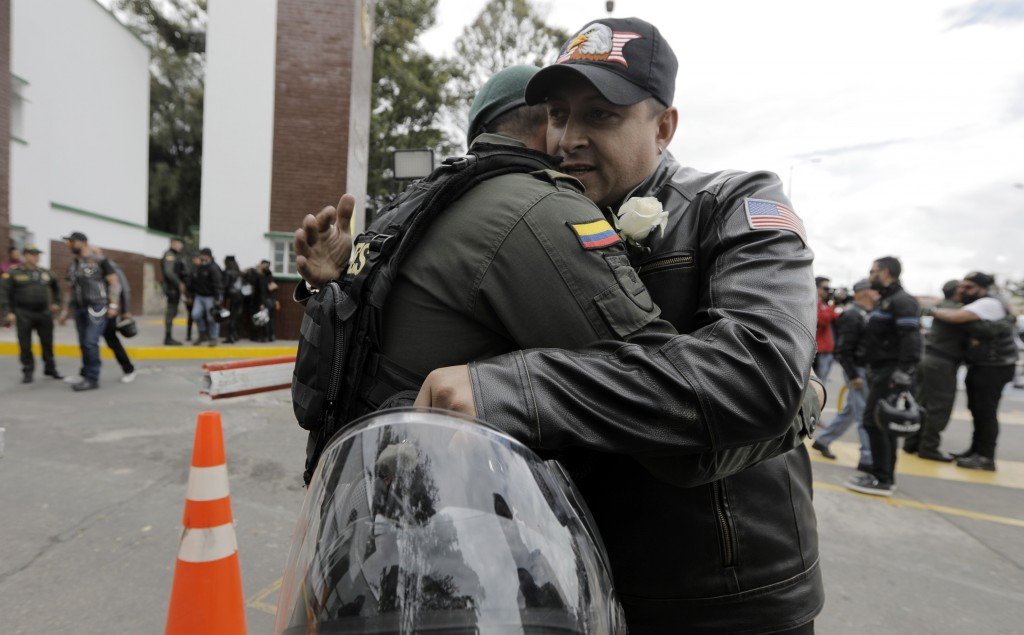 A man embraces a police officer, outside the General Francisco de Paula Santander Police Academy, a day after a car bomb exploded at the site, in Bogo...