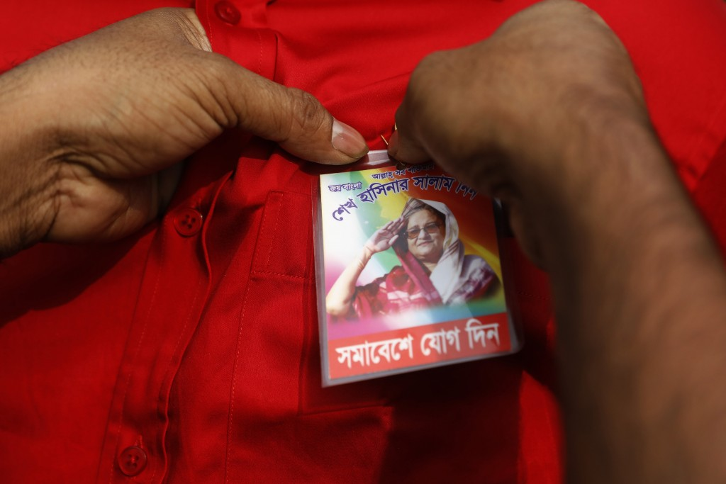 An Awami League political party supporter attaches a badge to the shirt of a fellow supporter during a rally to celebrate the party's overwhelming vic