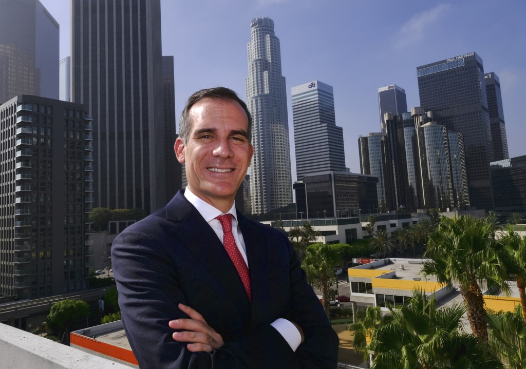 FILE - In this Aug. 23, 2018, file photo Los Angeles Mayor Eric Garcetti poses for a photo in front of a sprawling downtown Los Angeles landscape.  A
