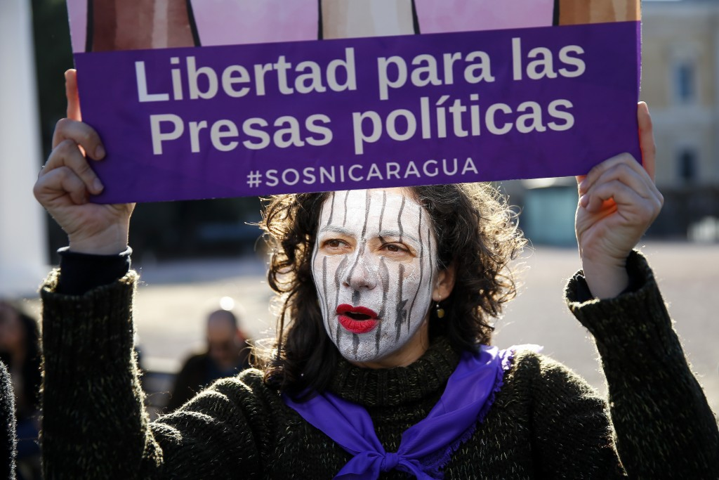 """FILE - In this Jan. 12, 2019 file photo, a demonstrator holds a placard reading in Spanish: """"Liberty for female political prisoners"""" during a protest"""