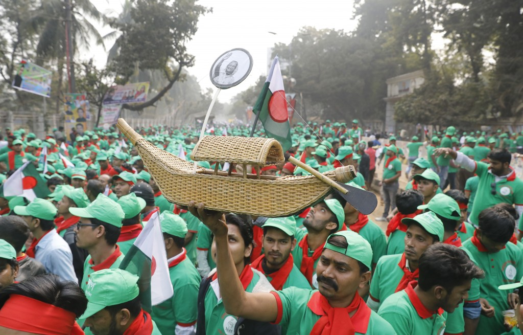 A supporter of the Awami League political party holds a miniature boat, the party's election icon, as they gather to attend a rally celebrating the ov