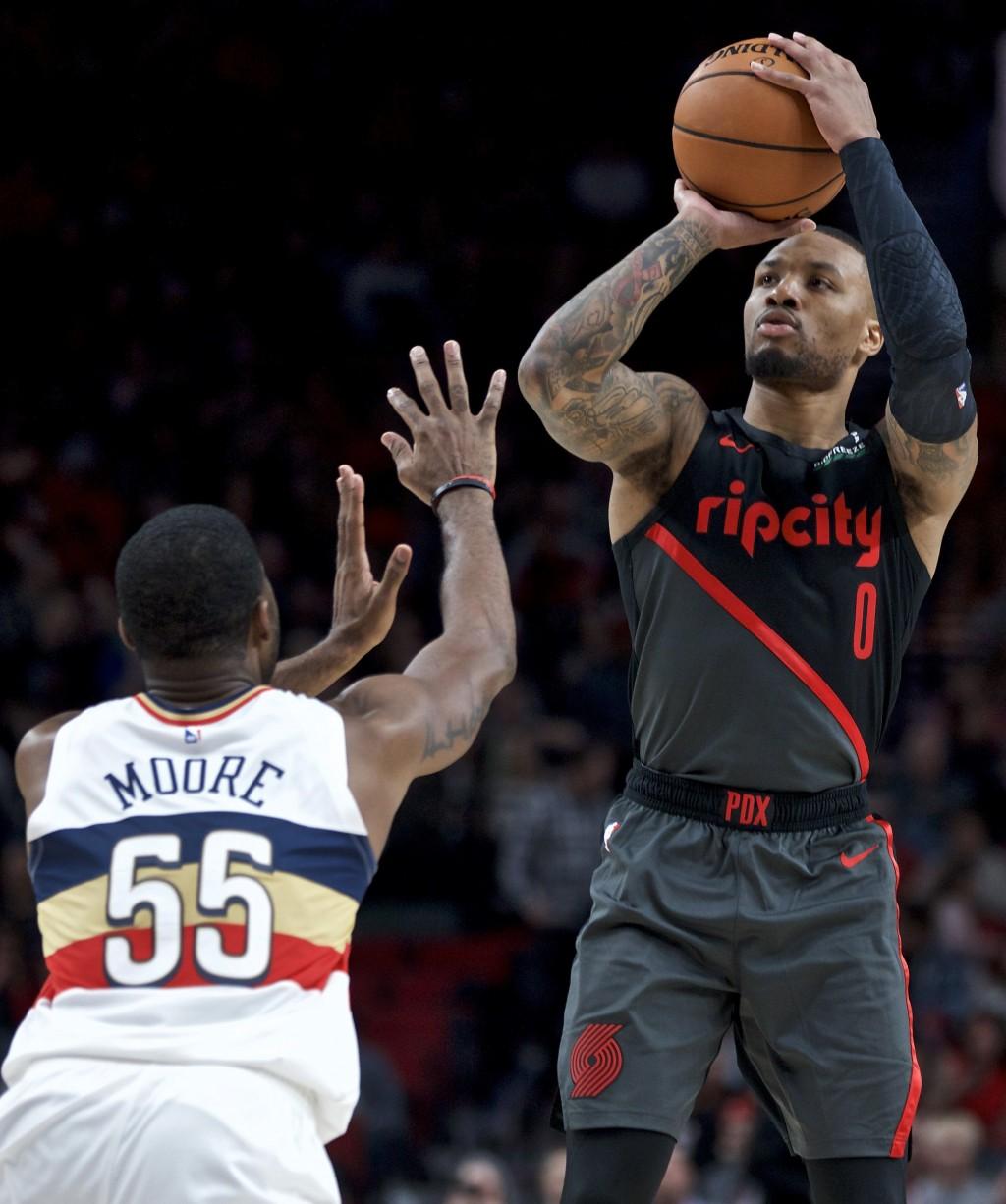 Portland Trail Blazers guard Damian Lillard, right, shoots over New Orleans Pelicans guard E'Twaun Moore during the second half of an NBA basketball g...