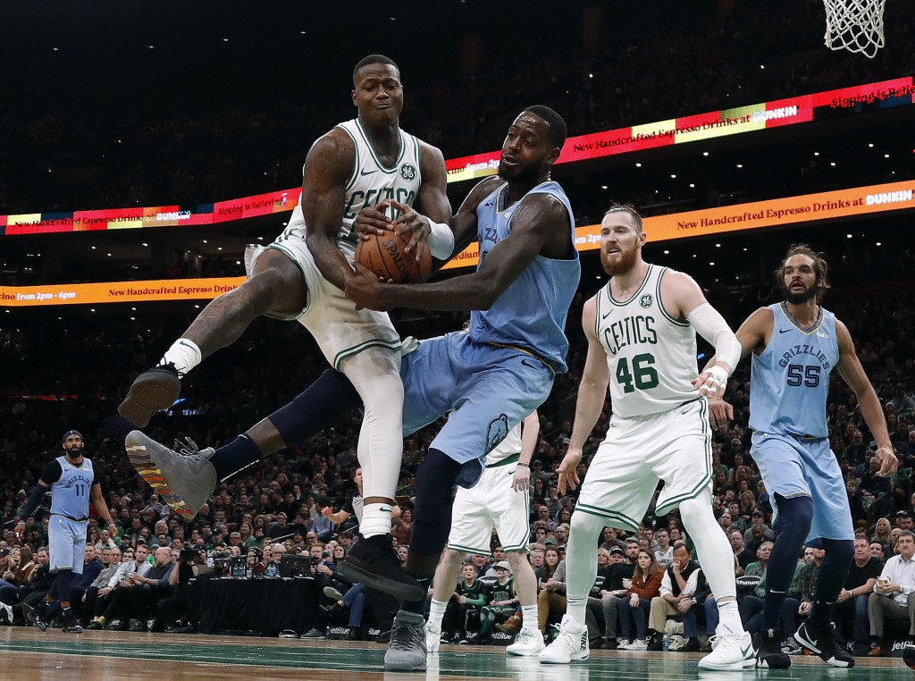 Boston Celtics' Terry Rozier and Memphis Grizzlies' JaMychal Green fight for a loose ball during the second half of an NBA basketball game Friday, Jan