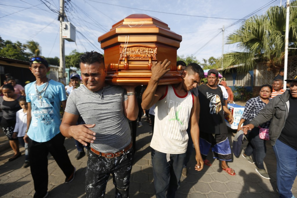 FILE - In this May 3, 2018 file photo, mourners, friends and family members carry the casket with the body of Nelson Tellez, who died of gunshot wound